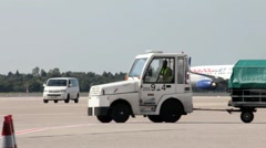 Aircraft taxiing and Tractor And Dollies Carrying Luggage Stock Footage