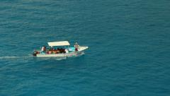 Small boat heading left to right on turquoise waters Stock Footage
