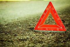 breakdown of car. red warning triangle sign on road - stock photo