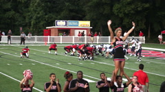 College cheerleaders in foreground with field goal in background Stock Footage