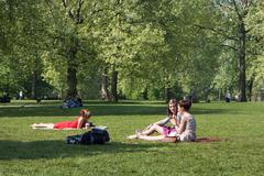 London - april 23: young students taking a lunch break in green park on april Stock Photos
