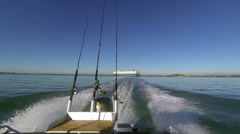 Gone fishing! Motor boat view looking back towards cargo ship. New Zealand. Stock Footage
