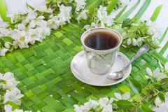 cup of coffee with the sprigs of flowering apple-tree - stock photo