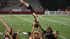 College cheerleaders at football game doing dangerous stunt - stock footage