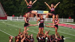 College cheerleaders at football game doing stunt - stock footage