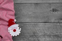 Red and white checkered fabric with santa head on grey wooden background for Stock Photos