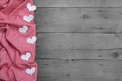 Red and white checkered frame with hearts on rustic wooden background - greet Stock Photos