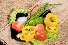 vegetables with greenery, rye bread and large salt on a dish - stock photo