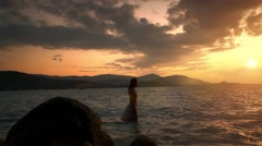 Woman walking in water and looking to the horizon over sea Stock Footage