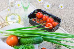 ripe red tomatoes and fresh greenery - stock photo