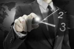 businessman navigating virtual clock - stock photo