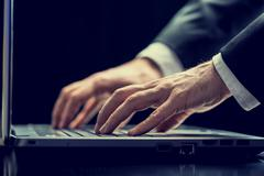 Businessman typing on a laptop in darkness Stock Photos