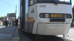 Tram in station people travel by public transport modern streetcar on rail track Stock Footage