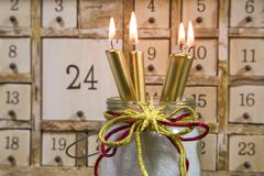 shabby chic advents calendar with four gold burning candles - stock photo