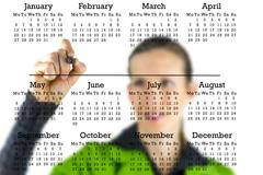 virtual calendar on a transparent interface with a woman writing from behind - stock photo