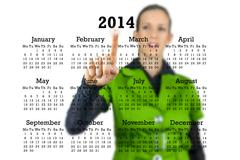 Woman standing behind a 2014 calendar on a transparent virtual interface Stock Photos