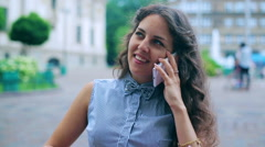 Beautiful woman speaking on the phone in the street cafe Stock Footage