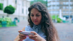 Woman tweeting on the phone in the street restaurant - stock footage