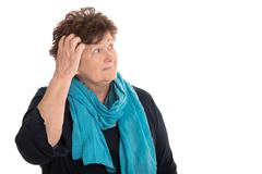 Isolated stunned senior woman looking pensive and sorrowful sideways. Stock Photos
