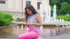 Stylish woman typing message on cellphone next to the fountain Stock Footage