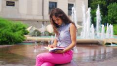 Woman finish reading book and relaxing next to the fountain Stock Footage