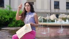 Woman sitting next to the fountain and reading map Stock Footage