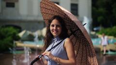 Woman spinning umbrella and smiling to the camera Stock Footage