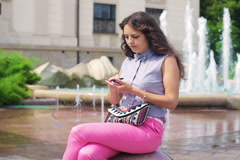 Woman sitting next to the fountain and improving makeup Stock Footage