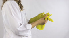 Girl in white robe smock take yellow rubber gloves off her hands Stock Footage
