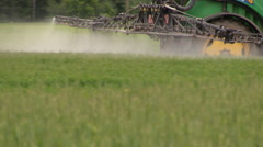 Follow tractor spray field plants with chemical pesticide Stock Footage