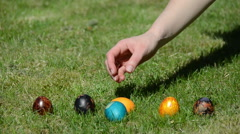 Traditional Easter game. Hand throw roll colorful eggs on grass. Stock Footage