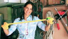 Happy woman showing tape measure to the camera in her garage Stock Footage