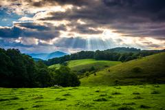 crepuscular rays over  a field and rolling hills at moses cone park on the bl - stock photo