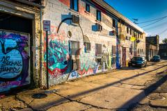 graffiti on walls in an alley in baltimore, maryland. - stock photo