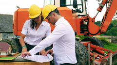 Couple of engineers discussing project on the consctruction site Stock Footage