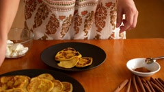 Woman Putting Pancakes on the Plate with Sour Cream and Cinnamon. Stock Footage