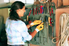Woman looking for pliers on the wall  - stock footage
