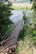 suspended bridge across the river - stock photo