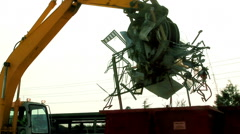 Excavator loads scrap metal junk into bin at garbage dump or recycling center. - stock footage