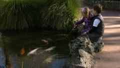 2 little children pretending to fish for Koi Carp. Stock Footage
