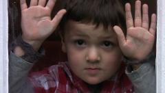 Child indoors on rainy day.  A lonely sad little boy looks through a wet window. Stock Footage