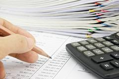 man is auditing account with pencil and calculator - stock photo