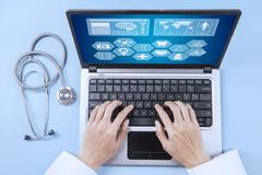 Doctor analyzing human illness on laptop Stock Photos