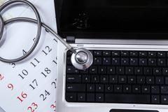 Laptop computer, stethoscope, and calendar Stock Photos