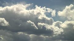 Bright cumulus clouds barrelling across the sky Stock Footage