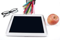 tablet pc with glasses, stationery, and apple - stock photo