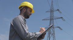 Write on clipboard engineer at electric high pole, notes and study case, working Stock Footage