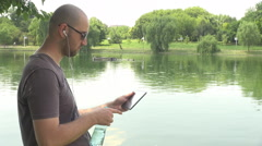 Stylish single man on lake edge, drinks water from plastic bottle, use tablet Stock Footage