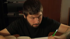 Tattooed Student Studying Late At Night, Cross Referencing, Exams, Front Tilt Stock Footage
