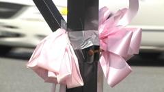 Pink ribbon closeup taped to metal pole daytime Stock Footage